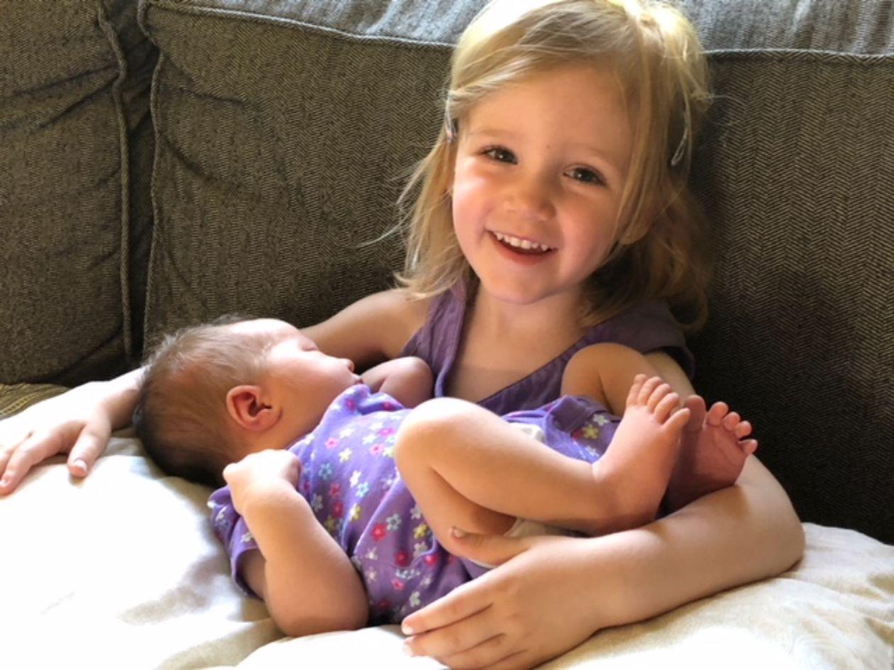 Bébé dans les bras d'une fillette