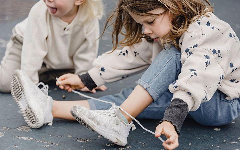 Motricité fine : fillette lace ses chaussures méticuleusement.