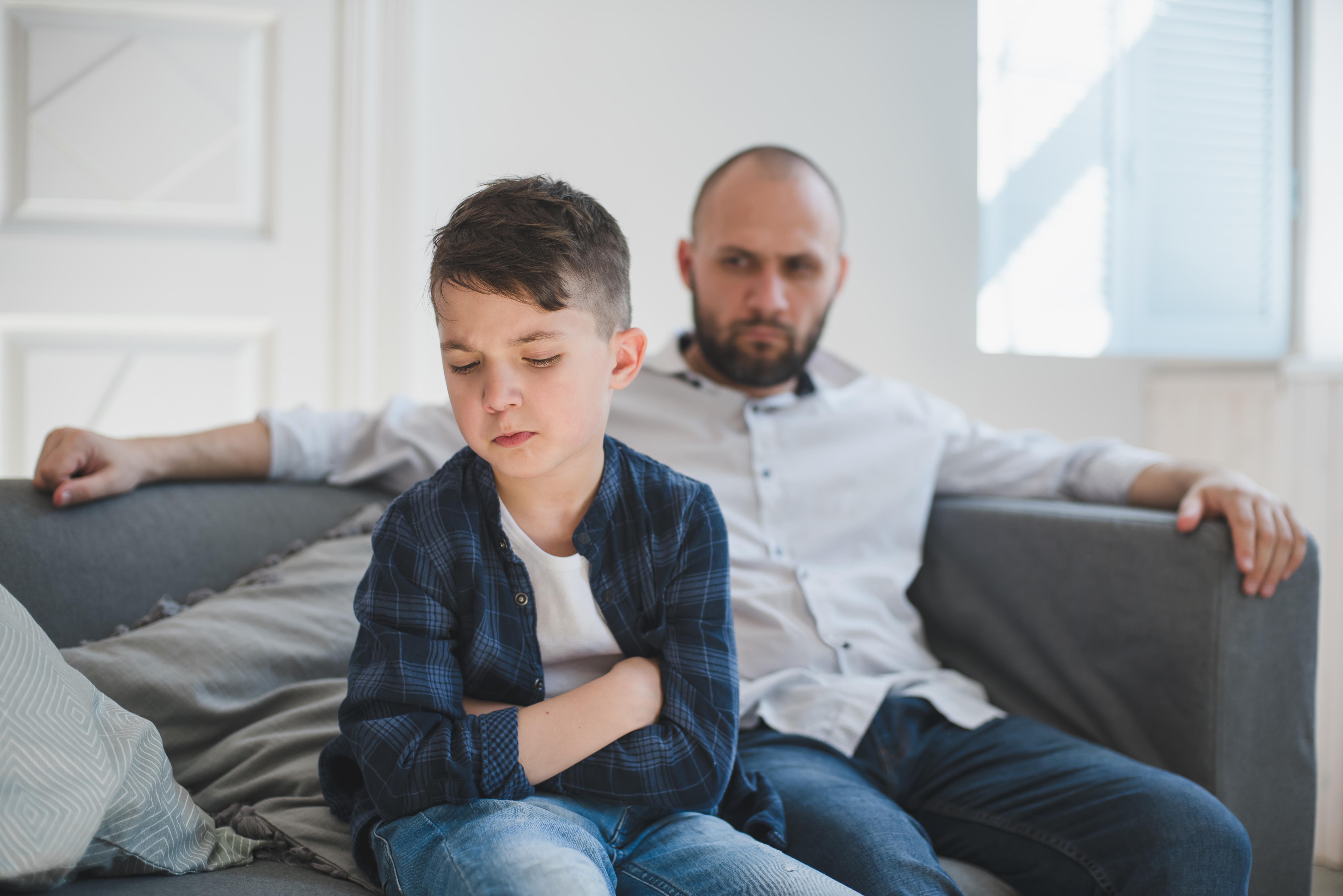 Un jeune garçon et son père son assis sur un sofa